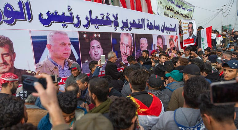 "Anti government Iraqi protesters gather by a banner with pictures of Iraqi politicians and Arabic that reads ""the Tahrir square questionnaire to select a prime minister,"" during the ongoing protests in Tahrir square, Baghdad, Iraq, Friday, Jan. 10, 2020."