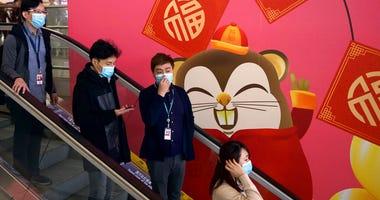 People wear face masks as they ride an escalator at the Hong Kong International Airport in Hong Kong, Tuesday, Jan. 21, 2020.  .(AP Photo/Ng Han Guan)