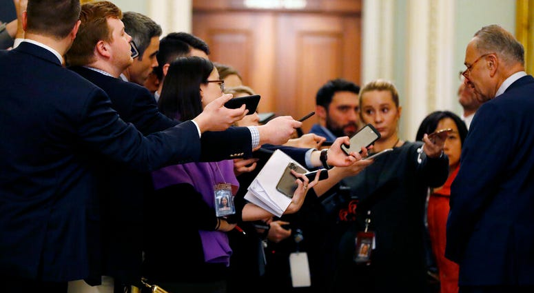 Reporters extend recording devices to Senate Minority Leader Chuck Schumer, D-N.Y., as he talks at the Capitol in Washington, Tuesday, Jan. 21, 2020. (AP Photo/Julio Cortez)