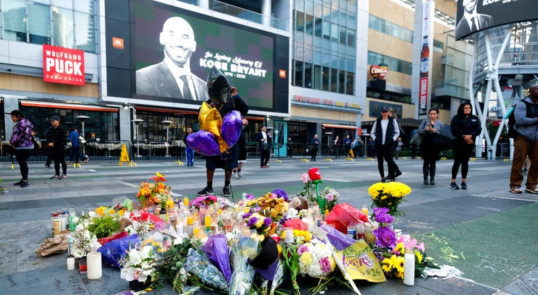 Flowers and candles are placed at a memorial for Kobe Bryant near Staples Center Monday, Jan. 27, 2020, in Los Angeles. (AP Photo/Ringo H.W. Chiu)