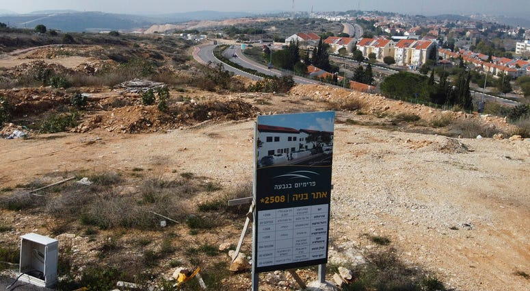 A new housing project sign stands in the Jewish West Bank settlement of Ari'el, Tuesday, Jan. 28, 2020. (AP Photo/Ariel Schalit)