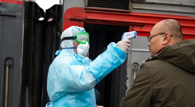 A medical worker in a hazardous materials suit uses a body thermal scanner to check temperature of Chinese passenger who just arrived from Beijing at the Yaroslavsky railway station in Moscow, Russia, Friday, Jan. 31, 2020. (AP Photo/Pavel Golovkin)