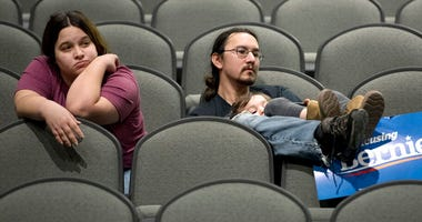 Jeff Lopez holds his son, Tristan, 4, as they and Jeff's wife, Jessika, sit in an area for Bernie Sanders supporters during the Woodbury County Third Precinct Democratic caucus, Monday, Feb. 3, 2020, at West High School in Sioux City, Iowa.