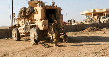 In this Feb. 23, 2017 file photo, U.S. Army soldiers stand outside their armored vehicle on a joint base with the Iraqi army, south of Mosul, Iraq. (AP Photo/ Khalid Mohammed, File)