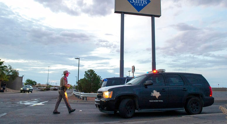In this Aug. 4, 2019 file photo, a Texas State Trooper walks back to his car while providing security outside the Walmart store in the aftermath of a mass shooting in El Paso, Texas.  (AP Photo/Andres Leighton)