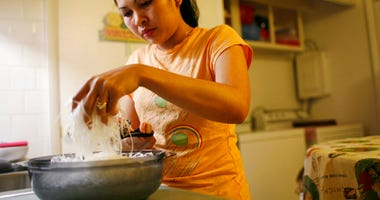 In this Nov. 21, 2007, photo, Elizabeth Keathley, a Philippine citizen in the U.S. on a marriage visa, cuts rice noodles as she prepares a traditional Filipino dish for dinner in Bloomington, Ill. (Abel Uribe/Chicago Tribune via AP)