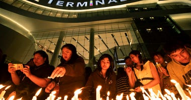 People attend a memorial service at the Terminal 21 Korat shopping mall in Nakhon Ratchasima, Thailand, Monday, Feb. 10, 2020. (AP Photo/Sakchai Lalit)