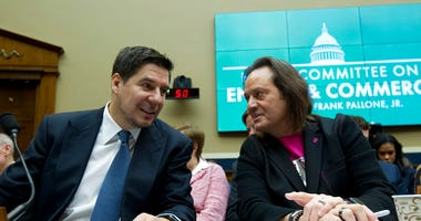 FILE - In this Feb. 13, 2019, file photo Sprint Corporation Executive Chairman Marcelo Claure, left, speaks with T-Mobile US CEO and President John Legere during the House Commerce subcommittee hearing on Capitol Hill in Washington. (AP Photo/Jose Luis Ma