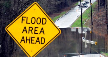 Vehicles turn around on a road blocked by floodwaters in Helena, Ala., on Tuesday, Feb. 11, 2020. (AP Photo/Jay Reeves)