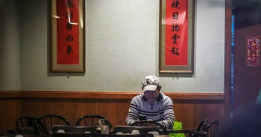 In this Feb. 13, 2020, photo, Frankie Chu, owner of Vegetarian Dim Sum House in New York's Chinatown, sits in his empty restaurant usually bustling with customers, in New York.  (AP Photo/Bebeto Matthews)
