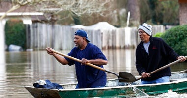 Jackson, Miss., homeowners use shovels to work their way through Pearl River floodwater in this Jackson, Miss., neighborhood Sunday, Feb. 16, 2020. (AP Photo/Rogelio V. Solis)