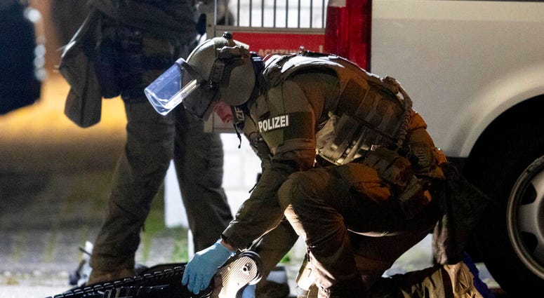 A special forces officer works on a robot in front of a house that is searched through by police in Hanau, Germany Thursday, Feb. 20, 2020. (AP Photo/Michael Probst)