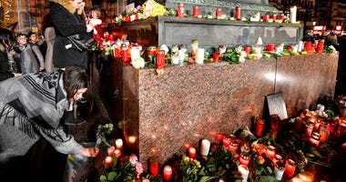 People place candles and flowers at a monument on the market place during a mourning for the victims of the shooting in Hanau, Germany, Thursday, Feb. 20, 2020. (AP Photo/Martin Meissner)