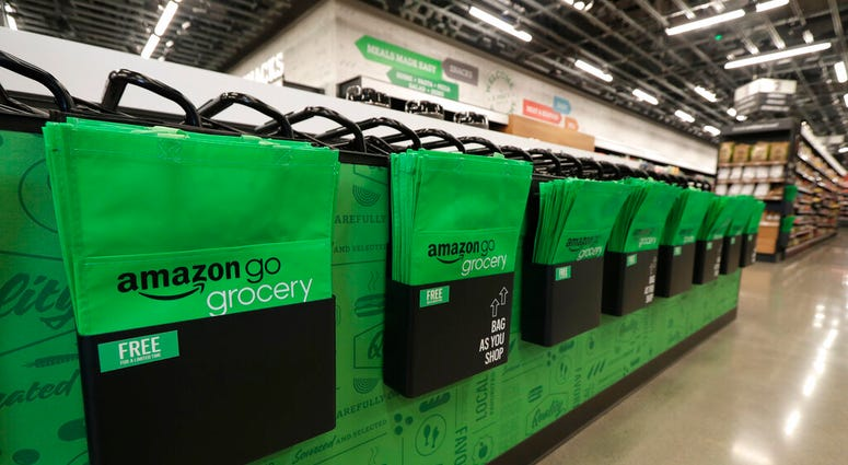 In this Feb. 21, 2020 photo, reusable shopping bags are displayed inside an Amazon Go Grocery store set to open soon in Seattle's Capitol Hill neighborhood. (AP Photo/Ted S. Warren)