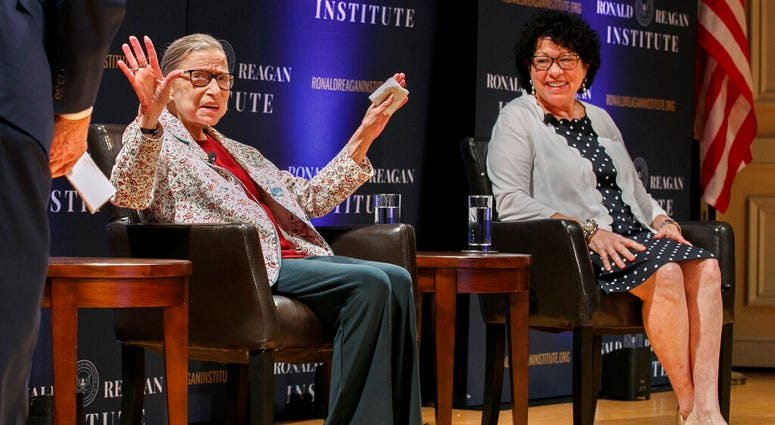 In this Sept. 25, 2019 file photo, Supreme Court Justice Ruth Bader Ginsburg, left, holds up her hands as she and Supreme Court Justice Sonia Sotomayor arrive to applause for a panel discussion.  (AP Photo/Jacquelyn Martin)