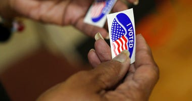 "An election officer passes out ""I Voted"" stickers during the Super Tuesday primary at at Lincoln Terrace Elementary School. (Heather Rousseau/The Roanoke Times via AP)"