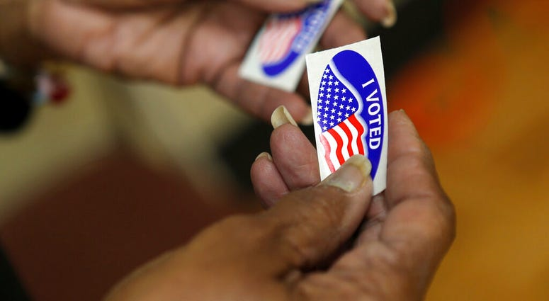 """An election officer passes out """"I Voted"""" stickers during the Super Tuesday primary at at Lincoln Terrace Elementary School. (Heather Rousseau/The Roanoke Times via AP)"""