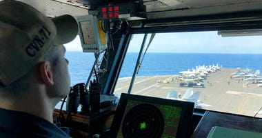 FILE - In this April 10, 2018, file photo, a U.S. Navy crewman monitors on the deck of the U.S. aircraft carrier Theodore Roosevelt in international waters off South China Sea.