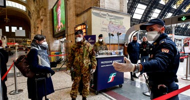 Police officers and soldiers check passengers leaving from Milan main train station, Italy, Monday, March 9, 2020. (Claudio Furlan/LaPresse via AP)