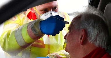 A member of the medical staff measures the temperature of a traveller at a autobahn park place near Gries am Brenner, Austrian province of Tyrol, at border crossing with Italy on Tuesday, March 10, 2020. (AP Photo/Kerstin Joensson )