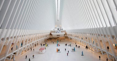 The Oculus at the World Trade Center's transportation hub is sparsely occupied, Monday, March 16, 2020 in New York. (AP Photo/Mark Lennihan)