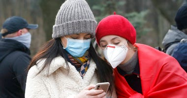 Ukrainians wearing face masks look at the latest news on a phone in Kyiv, Ukraine, Tuesday, March 17, 2020. (AP Photo/Efrem Lukatsky)