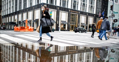 A pedestrian wearing a protective face mask is reflected in a rain puddle, Tuesday, March 17, 2020, in New York. New York state entered a new phase in the coronavirus pandemic this week, as New York City closed its public schools, and officials said schoo