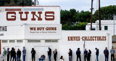People wait in a line to enter a gun store in Culver City, Calif., March 15, 2020.