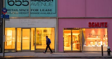 In this Thursday, March 19, 2020, photo, a pedestrian walks past a storefront for rent on Madison Avenue, in New York.  (AP Photo/Mary Altaffer)