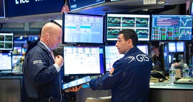 This photo provided by the New York Stock Exchange shows trader Patrick Casey, left, and specialist Peter Mazza as they work on the trading floor on Friday, March 20, 2020. (Nicole Pereira/NYSE via AP)