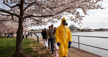 A 17-year-old who asked not to be named wears a yellow hazmat suit, gas mask, boots, and gloves as he walks with his family, from Gaithersburg, Md., under cherry blossom trees in full bloom along the tidal basin. (AP Photo/Jacquelyn Martin)