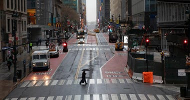 A commuter crosses 42nd Street in front of Grand Central Terminal during morning rush hour, Monday, March 23, 2020, in New York. (AP Photo/Mark Lennihan)