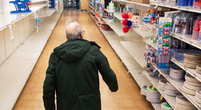 In this March 19, 2020 photo, a shopper looks for toilet paper at a Stop & Shop supermarket during hours open daily only for seniors in North Providence, R.I. (AP Photo/David Goldman)