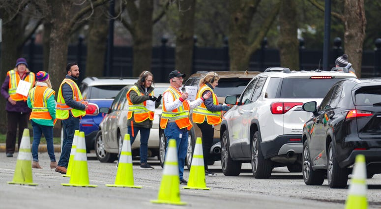 Employees of Eli Lilly check in members of the healthcare community as they begin drive-through testing for COVID-19, the disease caused by the new coronavirus, at the company headquarters in Indianapolis, Monday, March 23, 2020. (AP Photo/Michael Conroy)