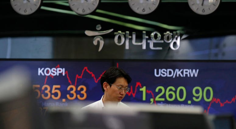 A currency trader walks by screens showing the Korea Composite Stock Price Index (KOSPI), left, and the foreign exchange rate between U.S. dollar and South Korean won at the foreign exchange dealing room in Seoul,  March 24, 2020. (AP Photo/Lee Jin-man)