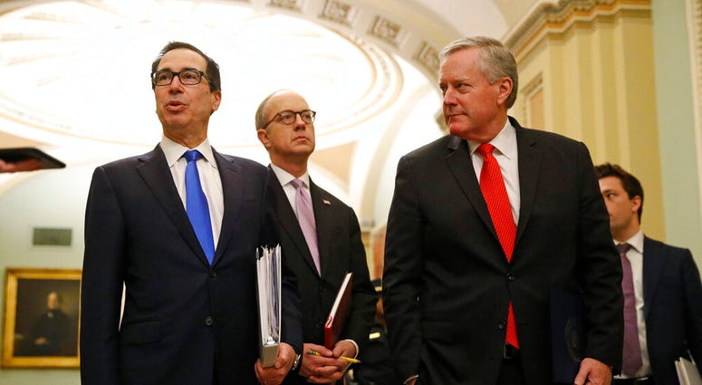 Treasury Secretary Steven Mnuchin, left, accompanied by White House Legislative Affairs Director Eric Ueland and acting White House chief of staff Mark Meadows. (AP Photo/Patrick Semansky)