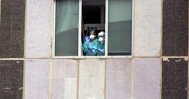 Medical workers wearing face masks gesture from hospital La Paz in Madrid, Spain. (AP Photo/Manu Fernandez, File)