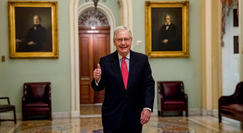 Senate Majority Leader Mitch McConnell of Ky. gives a thumbs up as he arrives on Capitol Hill, Wednesday, March 25, 2020, in Washington.