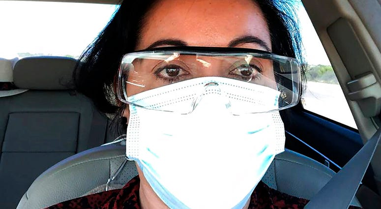 This March 23, 2020 photo provided by Margarita Silva shows her outside the La Palma Detention Center in Eloy, Ariz., wearing her husband's land surveyor goggles, a mask she borrowed from a friend and medical gloves she got from a hardware store