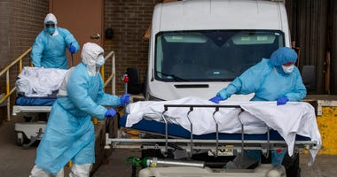 Medical personnel wearing personal protective equipment remove bodies from the Wyckoff Heights Medical Center Thursday, April 2, 2020 in the Brooklyn borough of New York.
