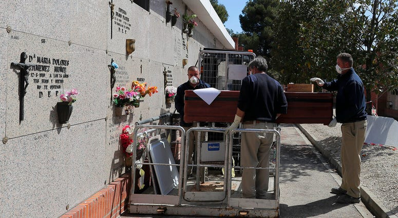 Undertakers carry the coffin of Rafael Catalan Villasanti, 83, during the coronavirus outbreak at the Carabanchel cemetery in Madrid, Spain, Saturday, April 4, 2020.