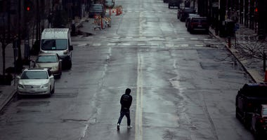 In this April 3, 2020, file photo a man crosses an empty street in downtown Kansas City, Mo. (AP Photo/Charlie Riedel, File)