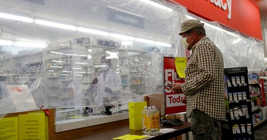 A customer waits for his medication behind a sheet of plastic installed to help curb the spread of the coronavirus at a CVS pharmacy store in Morton Grove, Ill., Tuesday, April 7, 2020.