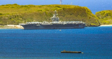 FILE - In this April 3, 2020, file photo, the USS Theodore Roosevelt, a Nimitz-class nuclear powered aircraft carrier, is docked along Kilo Wharf of Naval Base Guam.  (Rick Cruz/The Pacific Daily via AP, File)