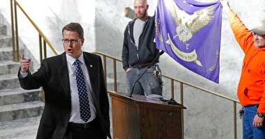 FILE - In this Friday, Feb. 15, 2019 file photo, Washington state Rep. Matt Shea, R-Spokane Valley, gestures as he gives a speech in front of the liberty state flag at the Capitol in Olympia, Wash. (AP Photo/Ted S. Warren, File)