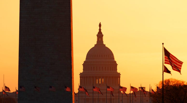 FILE - In this March 18, 2020, file photo, the Washington Monument and the U.S. Capitol are seen in Washington, at sunrise.