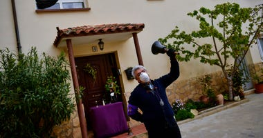 """Begona Diaz, 58, looks at her husband, Jose Mari Perez, 59, a member of """"Santa Vera Cruz'' brotherhood known as ''Los Picaos'' wearing a mask for protection while ringing a bell outside of his house on Maundy Thursday after celebrations were cancelled due"""