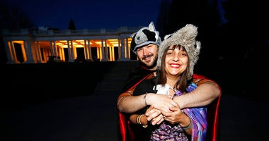 n this Wednesday, April 8, 2020, photograph, Brice Maiurro, back, hugs Shelsea Ochoa after they led a howl in Cheesman Park in Denver as a statewide stay-at-home order remained in effect in an effort to reduce the spread of the coronavirus.