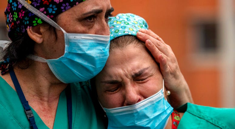 Health workers cry during a memorial for their co-worker Esteban, a male nurse that died of the coronavirus disease, at the Severo Ochoa Hospital in Leganes in Leganes, Spain, Friday, April 10, 2020.