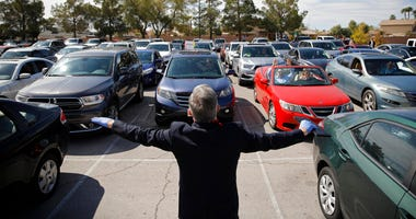 Pastor Paul Marc Goulet prays to people in their cars at an Easter drive-in service at the International Church of Las Vegas due to the coronavirus outbreak, Sunday, April 12, 2020, in Las Vegas.